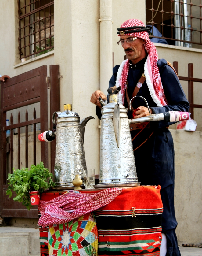 A traditional bedouin man making cardamom coffee for the visitors.
