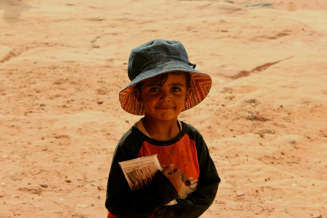 A small kid 5 years old helping his mother sell some postcards for 1 jordanian dinnar. Living amongst this sand and rocks is all he has seen and known.